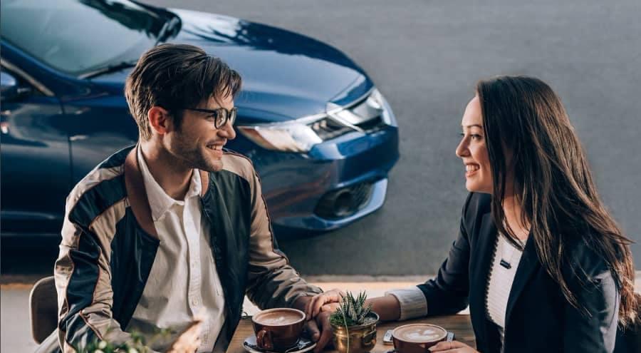Couple have coffee near acura