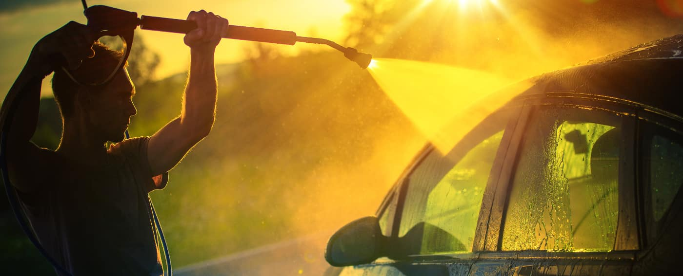 man washes car with power washer