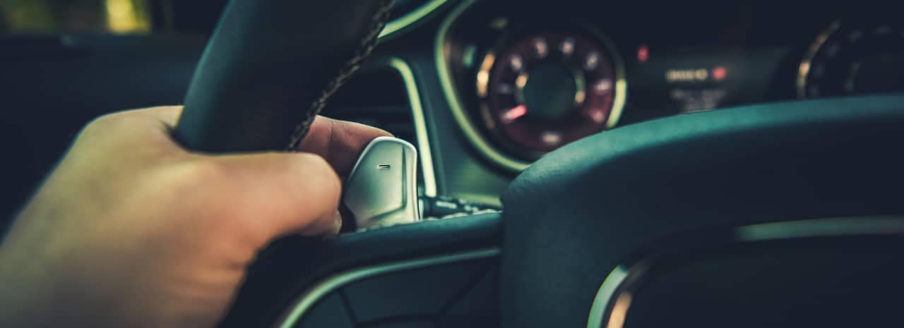 person uses Paddle Shifters in car