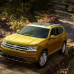 Yellow Volkswagen Atlas parked on a shadowy road near trees and shrubbery