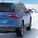 Blue 2019 Volkswagen Tiguan driving over snow with mountains in background