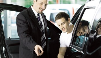 Salesmen showing a cars features