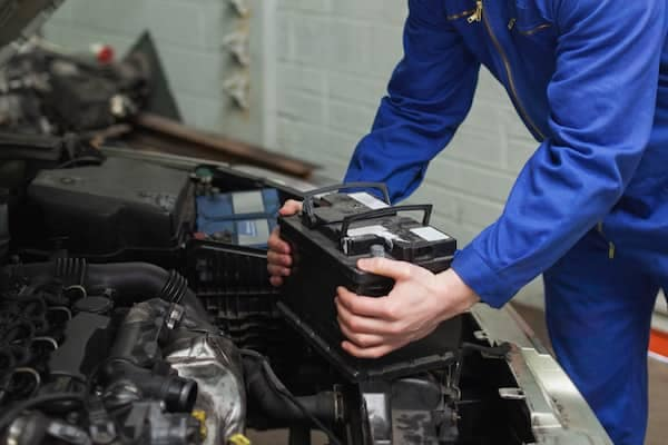 Service tech removing or replacing car battery
