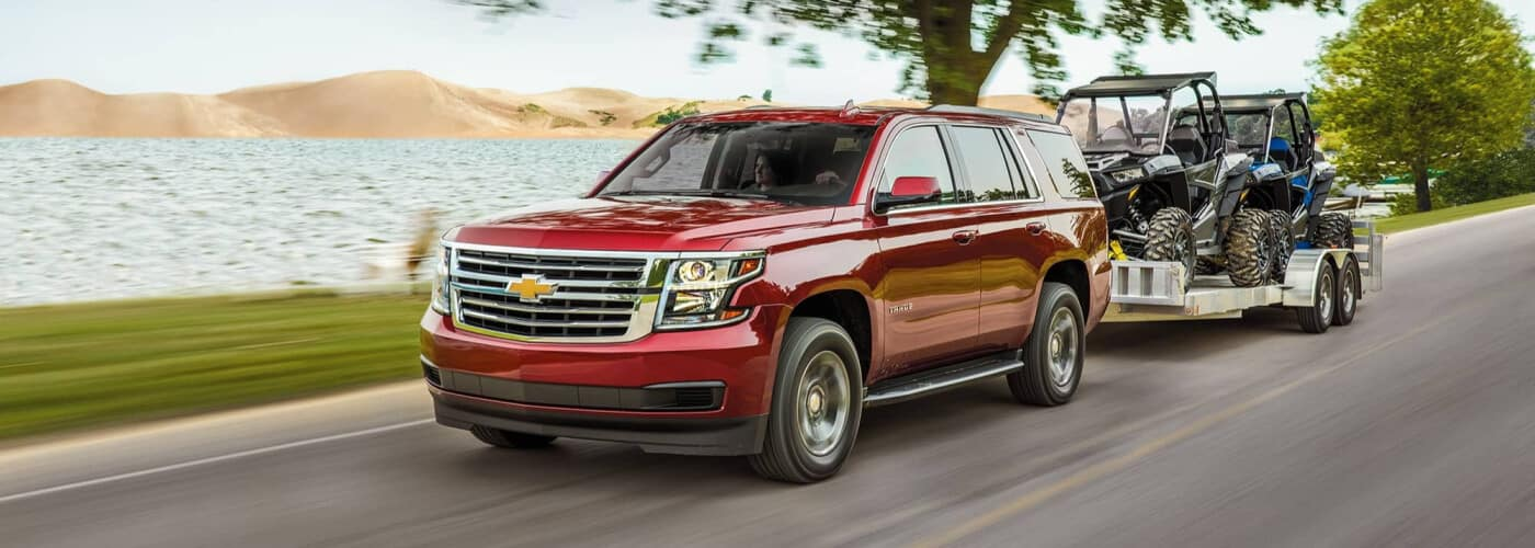 Red 2019 Chevy Tahoe Towing a pair of ATVs