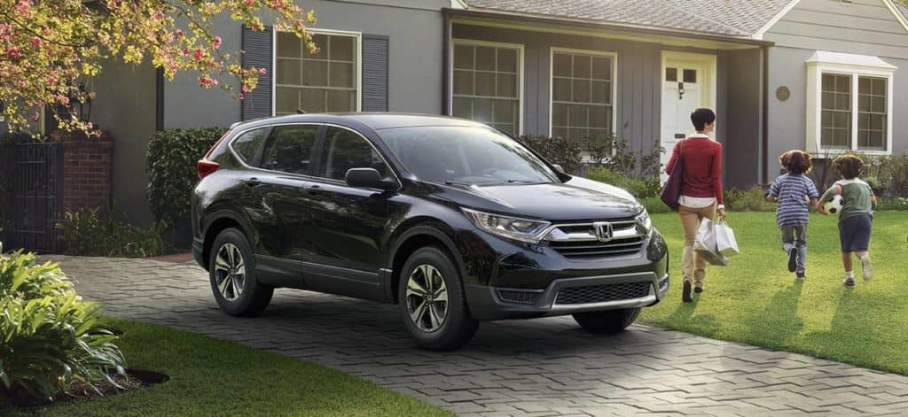 2018 Honda CR-V parked in driveway as family walks into house
