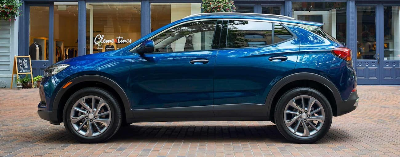 A blue 2021 Buick Encore GX is shown from the side on a city street.