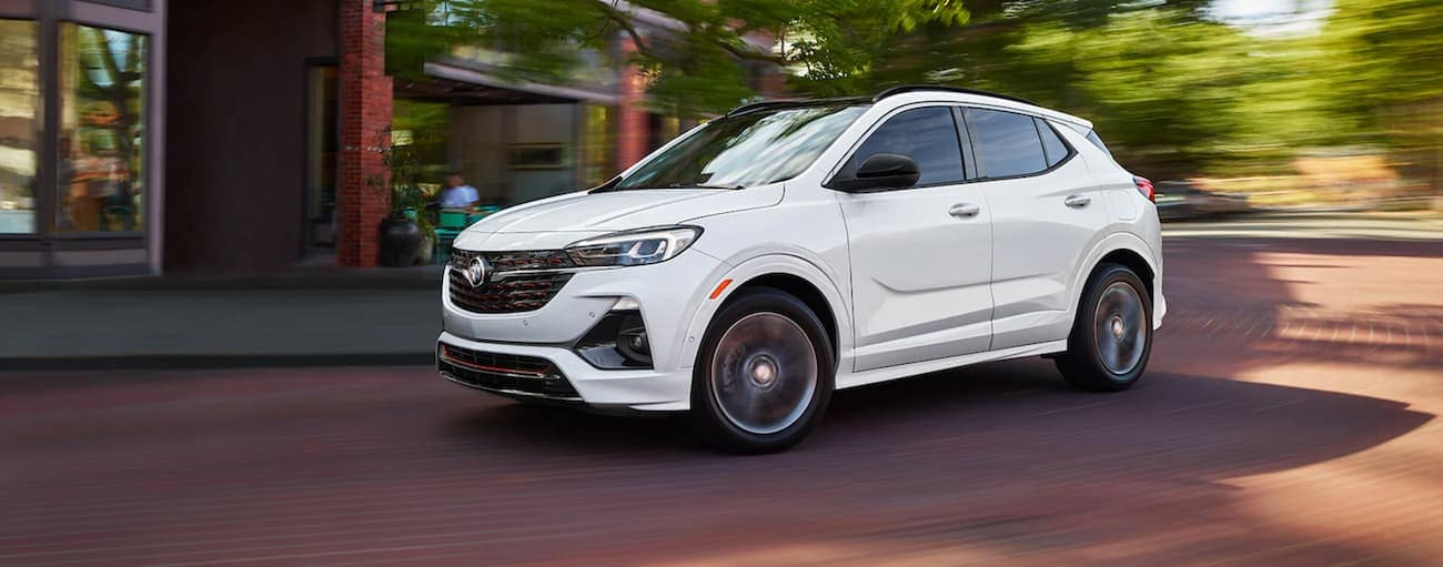 A white 2021 Buick Encore GX Sport Touring is driving on a brick road.