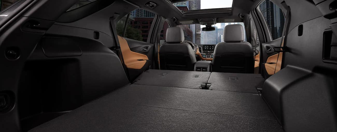 The black and brown interior in a 2021 Chevy Equinox is shown with the seats down.