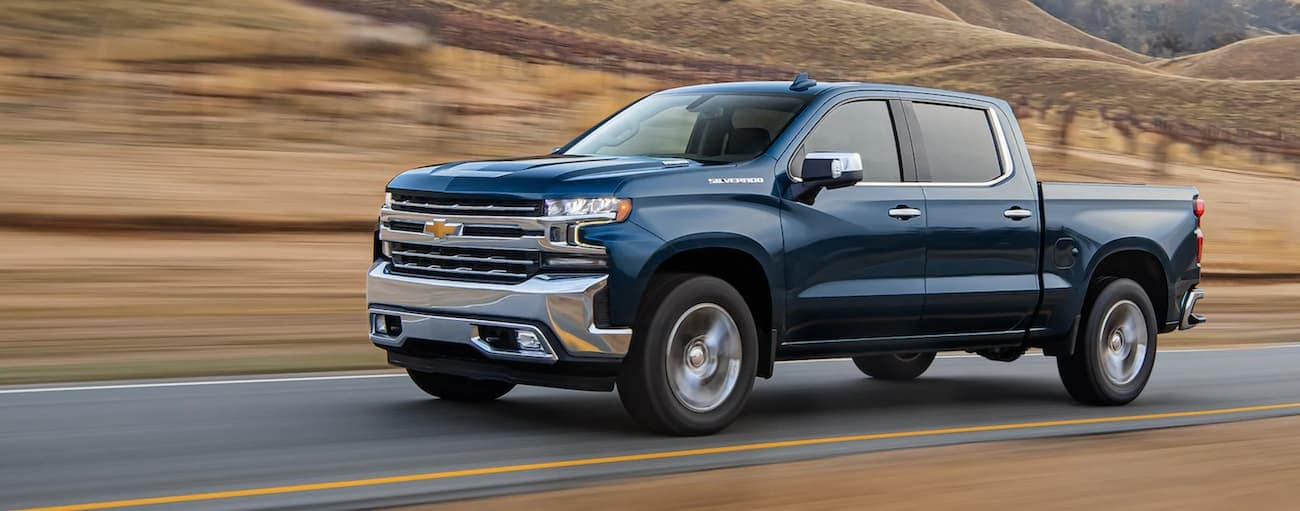 A blue 2021 Chevy Silverado 1500 is driving on a one lane road past hills with brown grass.
