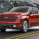 A red 2021 Chevy Silverado is shown driving down the highway after leaving a Louisville Chevy dealer.