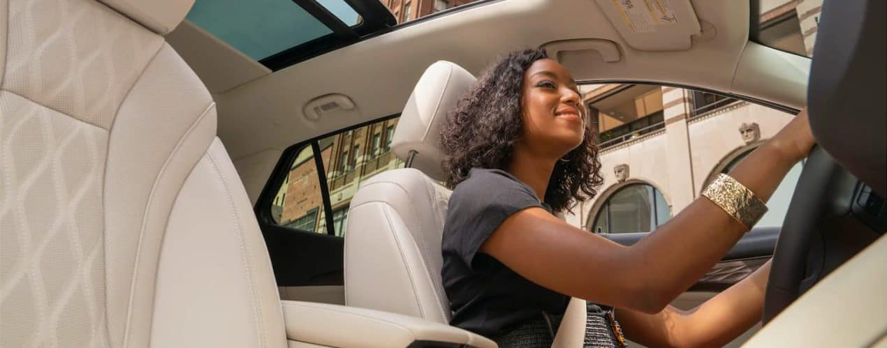 A woman is shown for a low angle driving a 2021 Buick Envision Avenir.