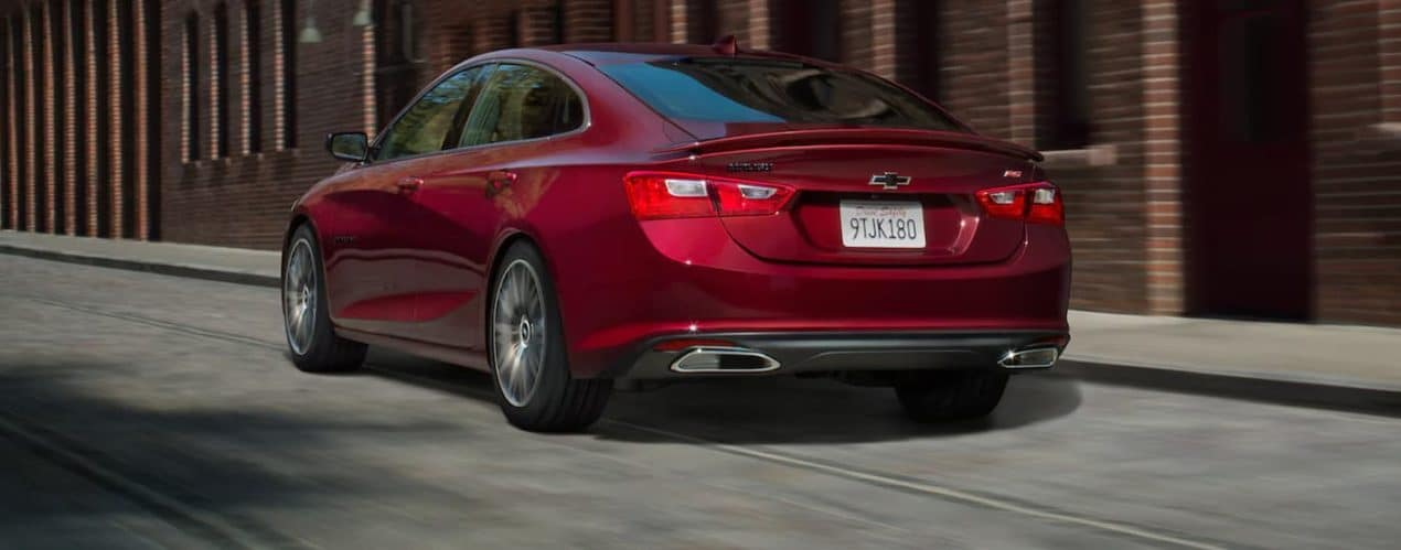 A red 2021 Chevy Malibu is shown from the rear driving down a city street past a brick building.