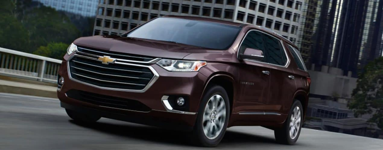A brown 2021 Chevy Traverse is shown from the front driving past buildings in the city.