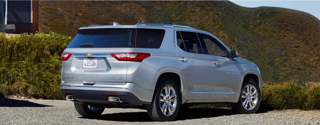 A silver 2021 Chevy Traverse is shown from behind overlooking mountains.