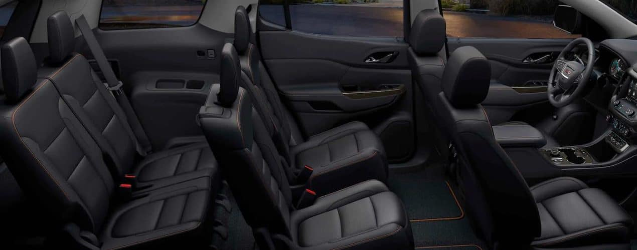 The black interior is shown from the side on a 2021 GMC Acadia.
