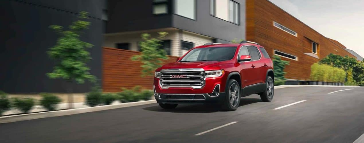 A red 2021 GMC Acadia is driving down a city street past modern houses.