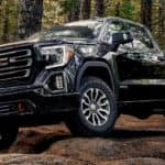 A black 2019 GMC Sierra AT4 is off-roading in the woods.