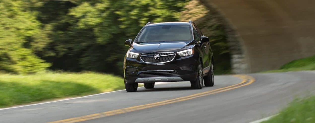 A black 2021 Buick Encore is driving around a corner in front of a bridge.