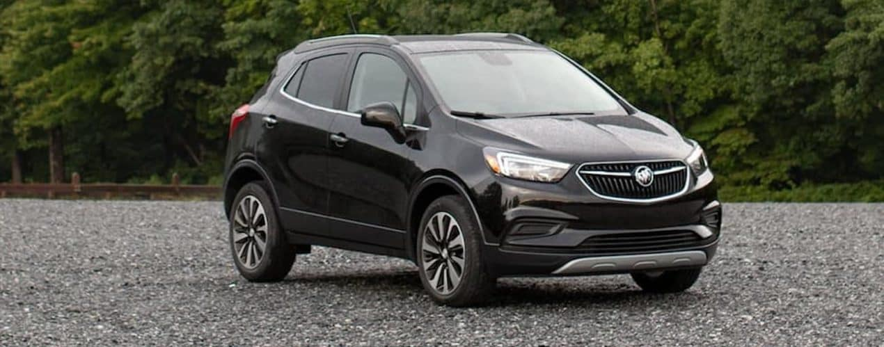 A black 2021 Buick Encore is parked in an open lot in front of trees.