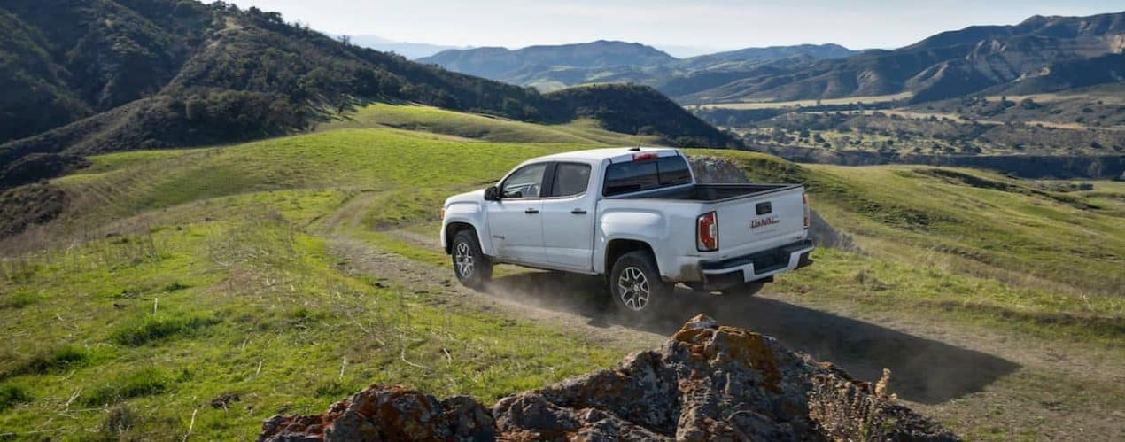 A white 2021 GMC Canyon is off-roading on a path toward mountains.