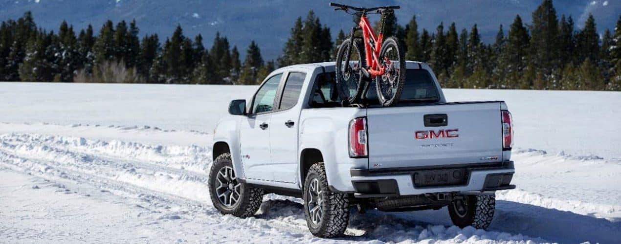A white 2021 GMC Canyon is in snow with a red bike on racks in the bed.