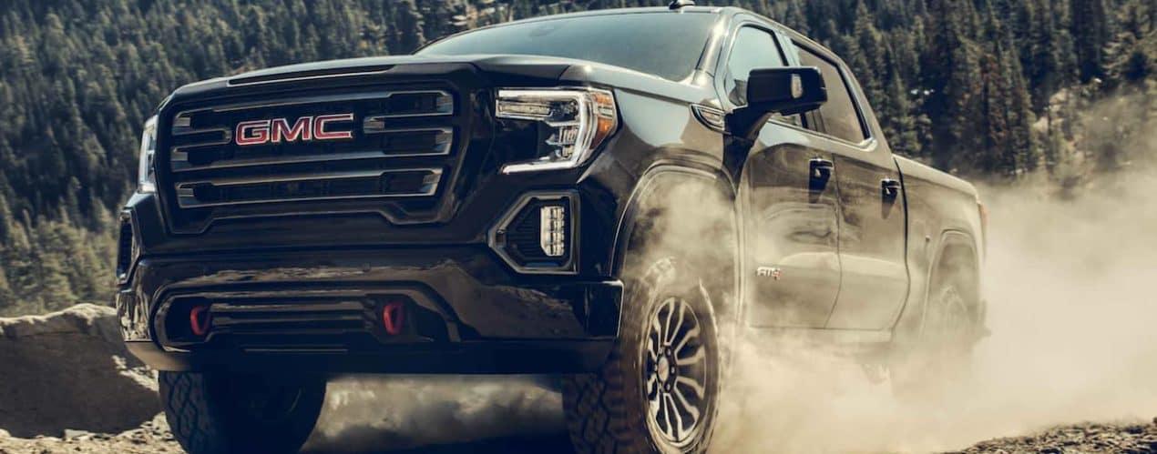 A black 2021 GMC Sierra 1500 is kicking up dust on a dirt road.