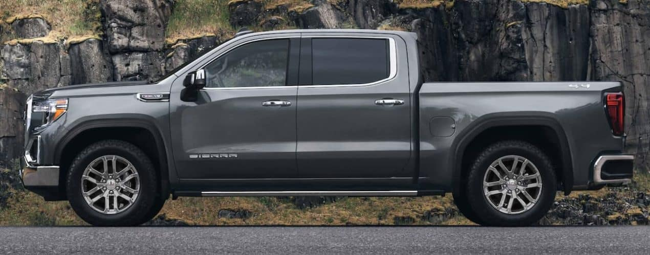 A grey 2021 GMC Sierra 1500 is shown from the side in front of grass covered rock.