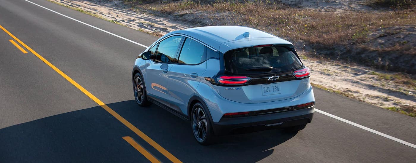 A silver 2022 Chevy Bolt EV is shown from behind driving down an empty road.
