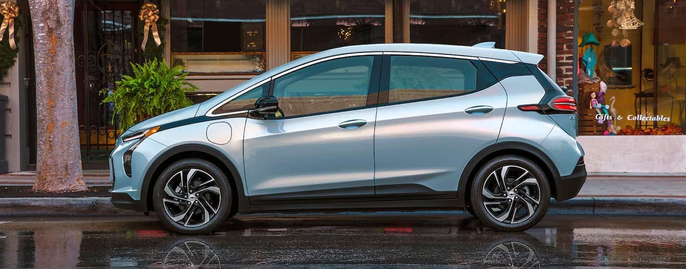 A pale blue 2022 Chevy Bolt EV is shown from the side parked outside a shop.