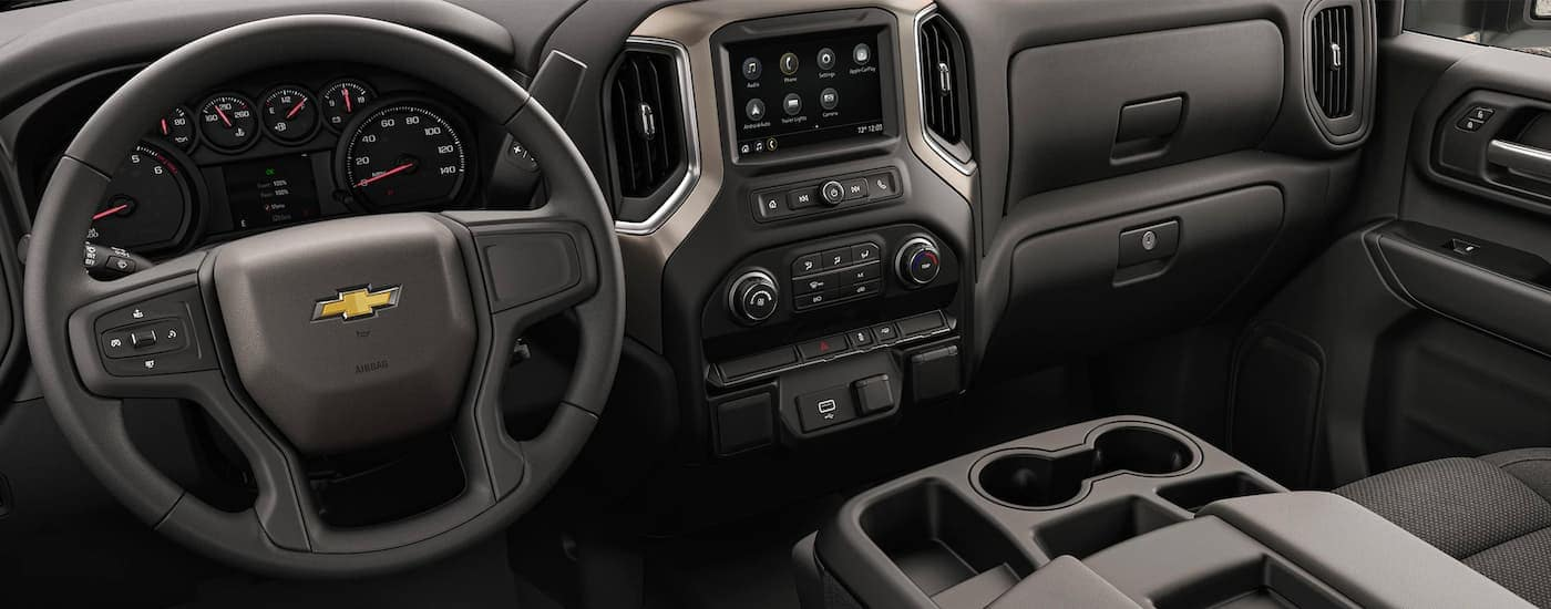 The black interior front seats and dashboard is shown in a 2021 Chevy Silverado 3500 HD.