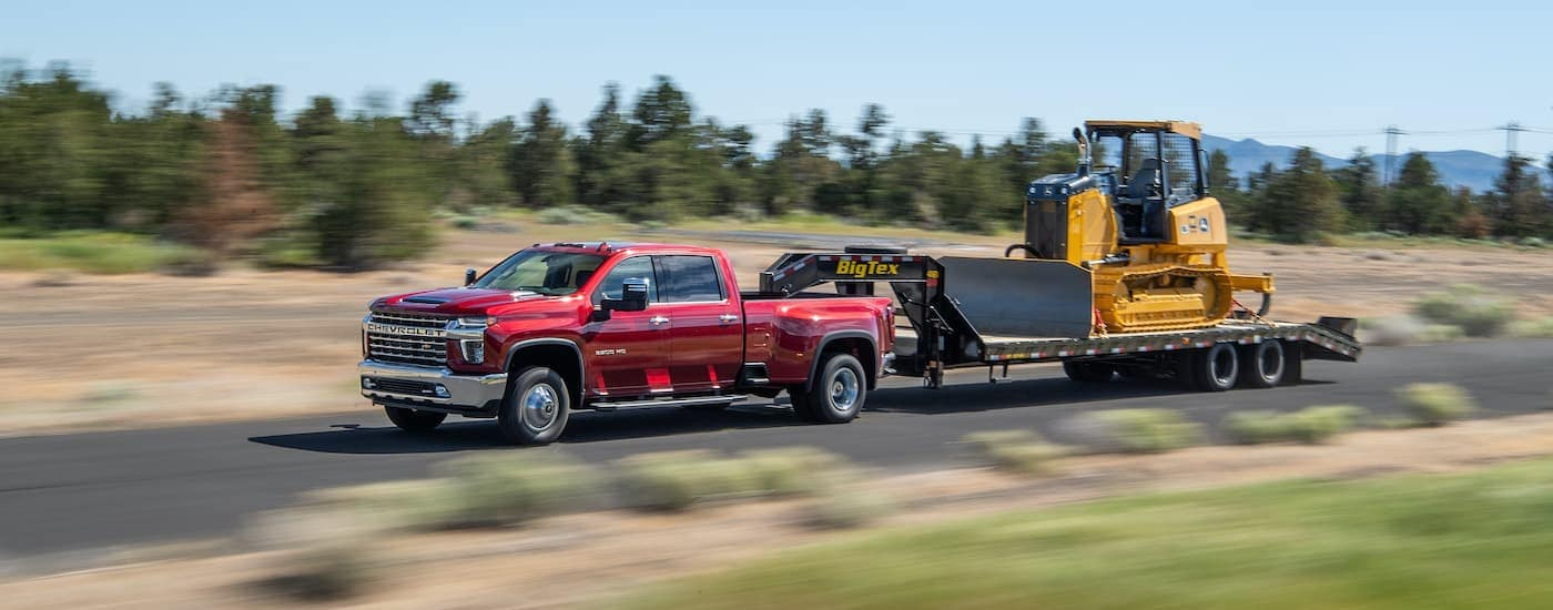 A red 2021 Chevy Silverado 3500 HD is shown from the side towing a gooseneck trailer with construction equipment.