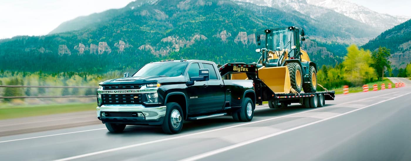 A black 2021 Chevy Silverado 3500 HD is shown from the side towing a trailer with construction equipment down an empty highway.