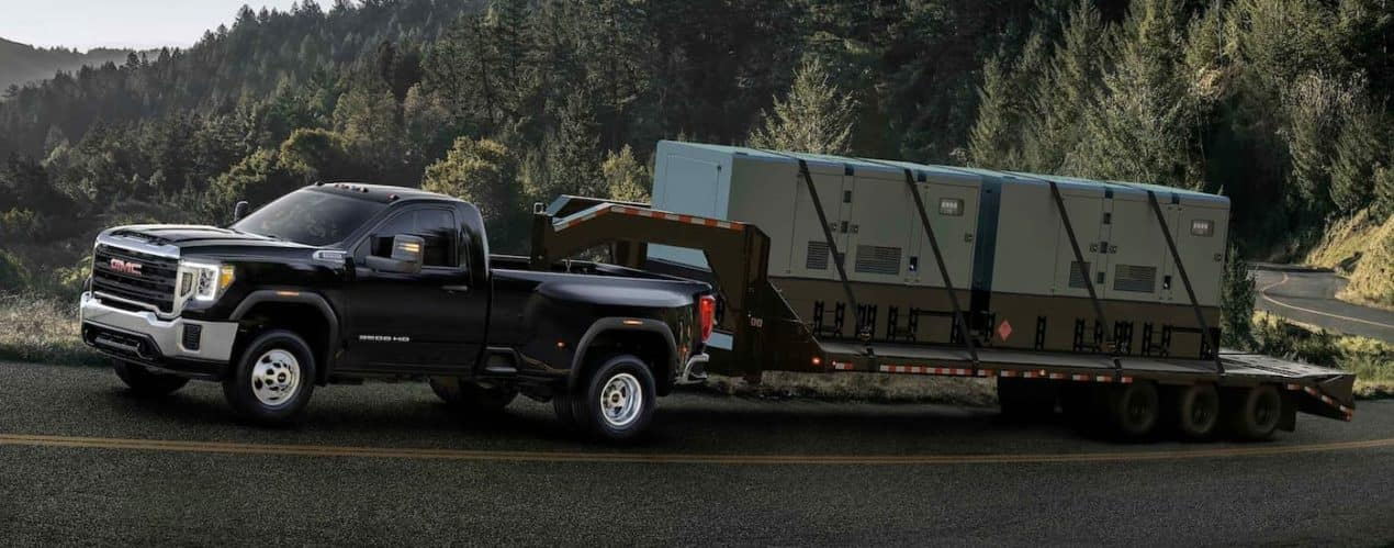 A black 2021 GMC Sierra 3500HD is shown from the side driving up a mountain with a gooseneck trailer.