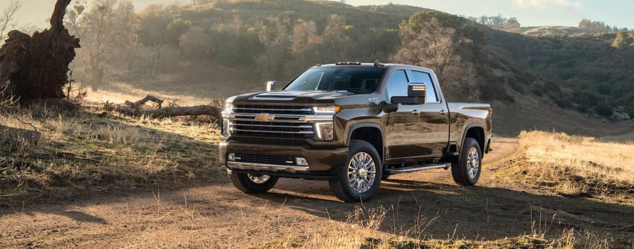 A black 2021 Chevy Silverado 2500 HD High Country is shown parked on a dirt path near hills.