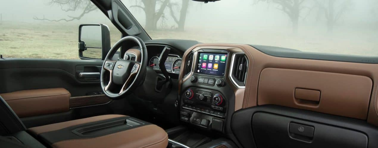 The black interior and infotainment screen are shown in a 2021 Chevy Silverado 2500 HD High Country.