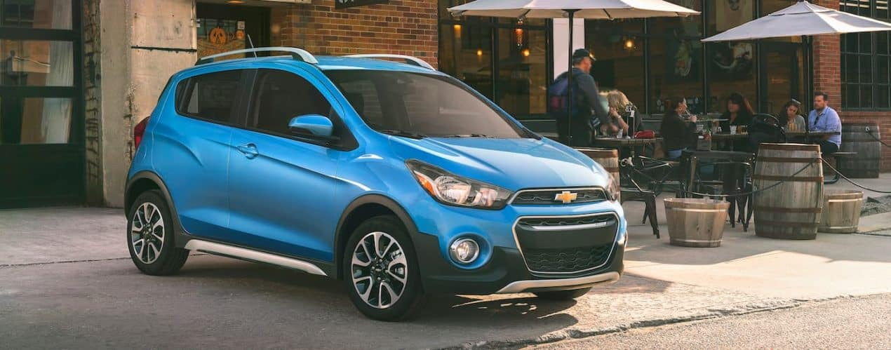 A blue 2021 Chevy Spark ACTIV is shown parked outside of a cafe.