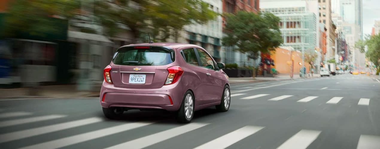 A magenta 2021 Chevy Spark is shown from the rear driving down a city street.
