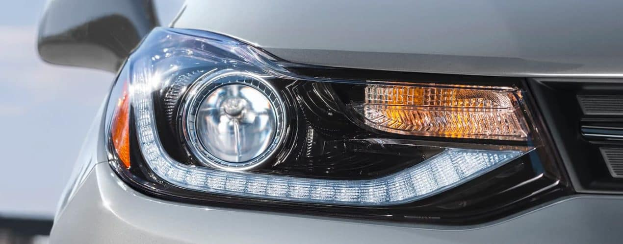 A close up shows the headlight on a silver 2021 Chevy Trax.