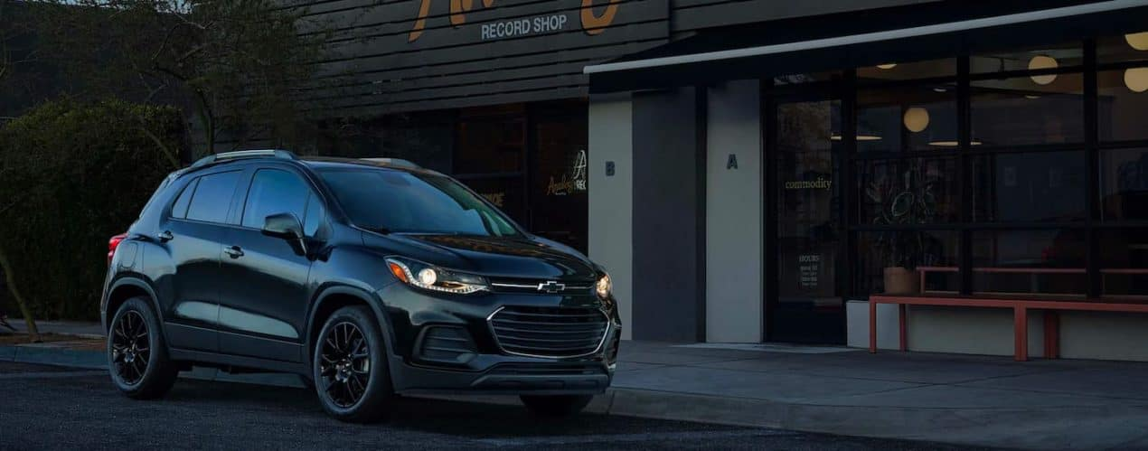 A black 2021 Chevy Trax is shown parked outside of a record store.