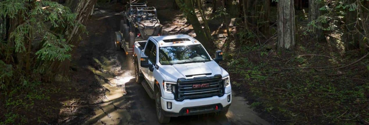 A white 2021 GMC Sierra 2500 HD AT4 is shown from a high angle towing UTVs through the woods.