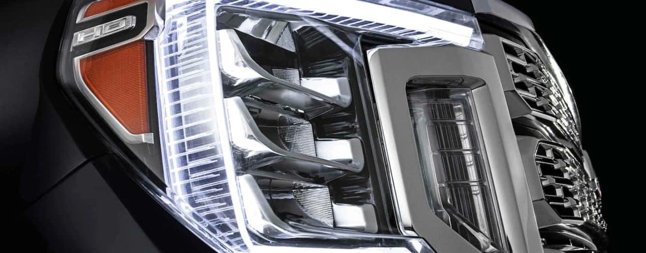 A close up shows the headlight on a black 2021 GMC Sierra 2500 HD Denali.