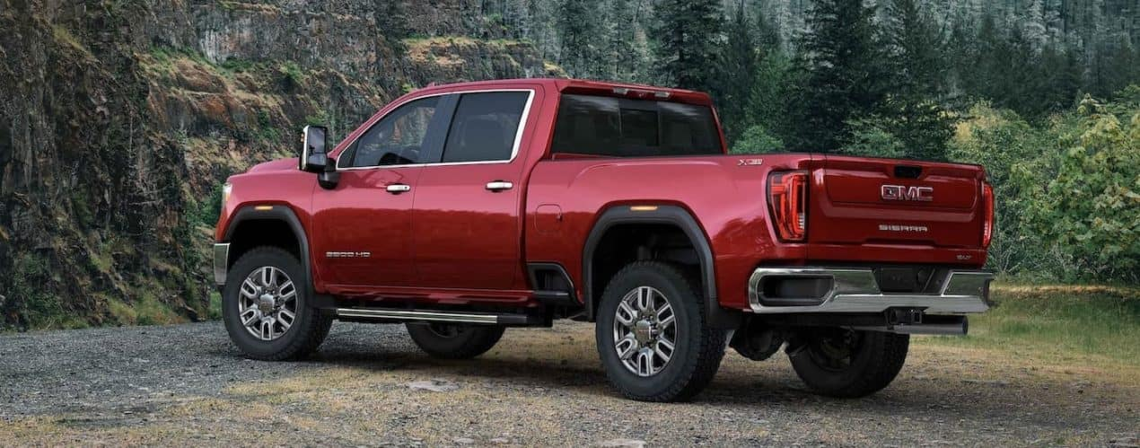 A red 2021 GMC Sierra 2500 HD SLT is shown from the side parked in the woods.