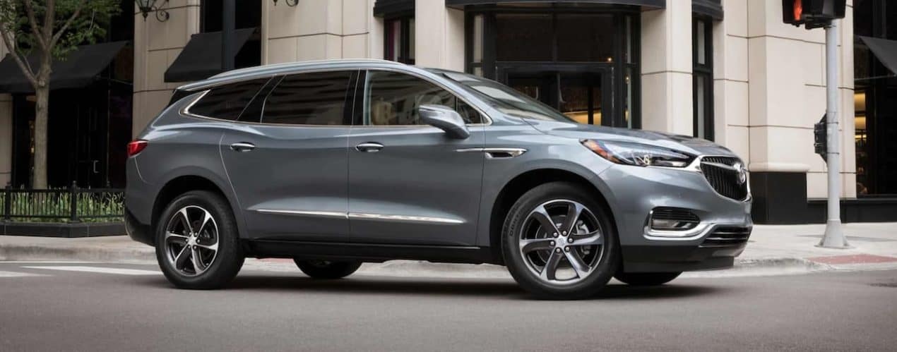 A grey 2021 Buick Enclave is shown from the side driving through a city.
