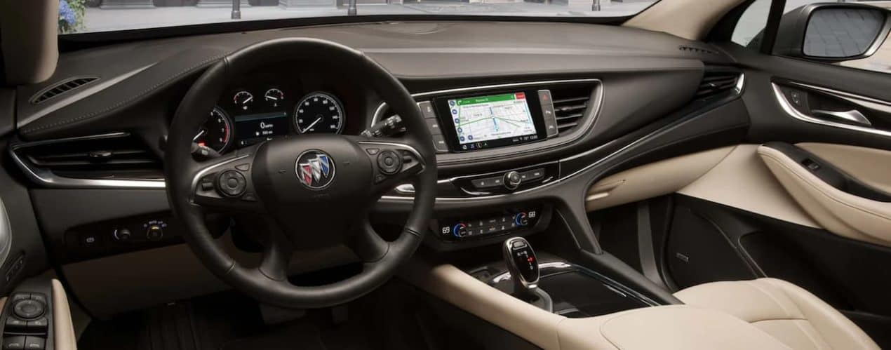 The tan interior of a 2021 Buick Enclave shows the steering wheel and infotainment system.