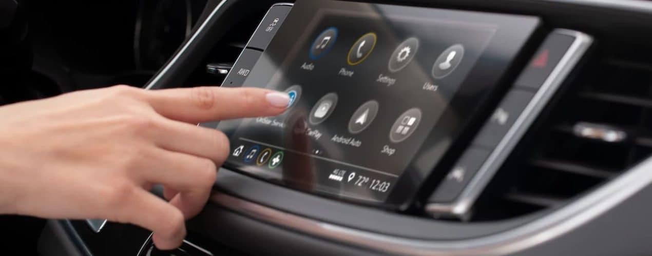A person is using the touch screen in a 2021 Buick Enclave.
