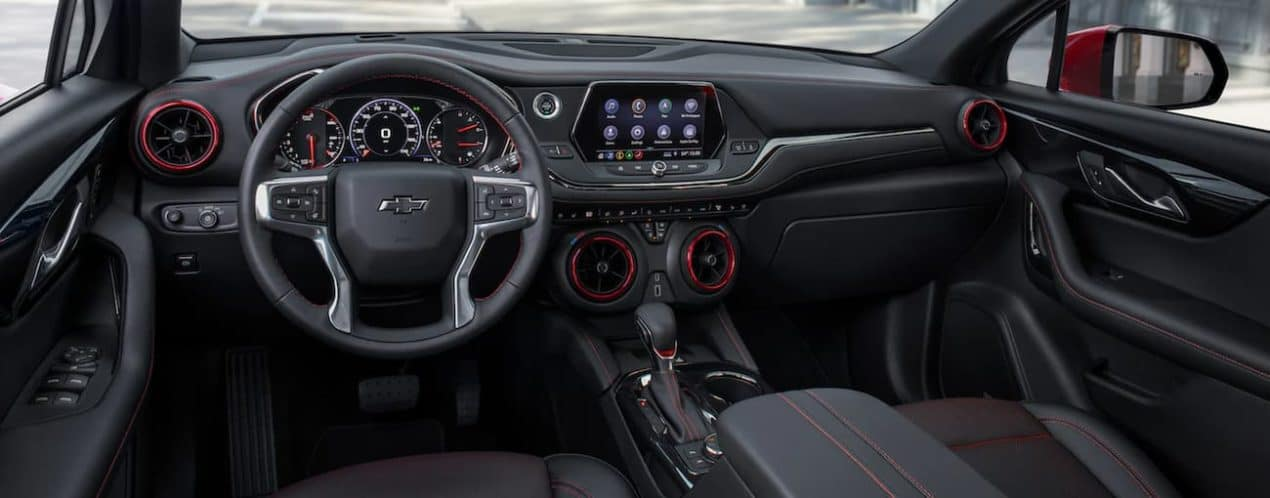 The black 2021 Chevy Blazer shows the steering wheel and infotainment screen.