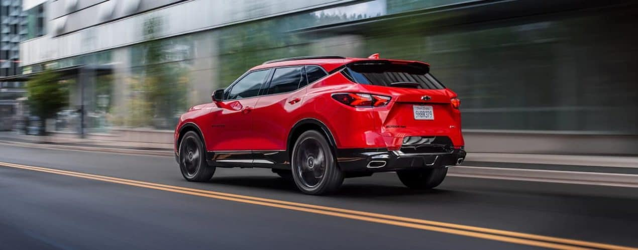 A red 2021 Chevy Blazer is shown from the side driving through a city.