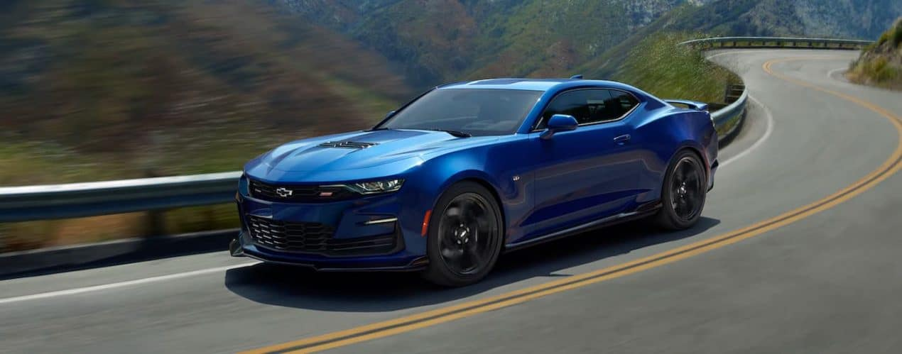 A blue 2021 Chevy Camaro 2SS Coupe is shown driving down an empty street.