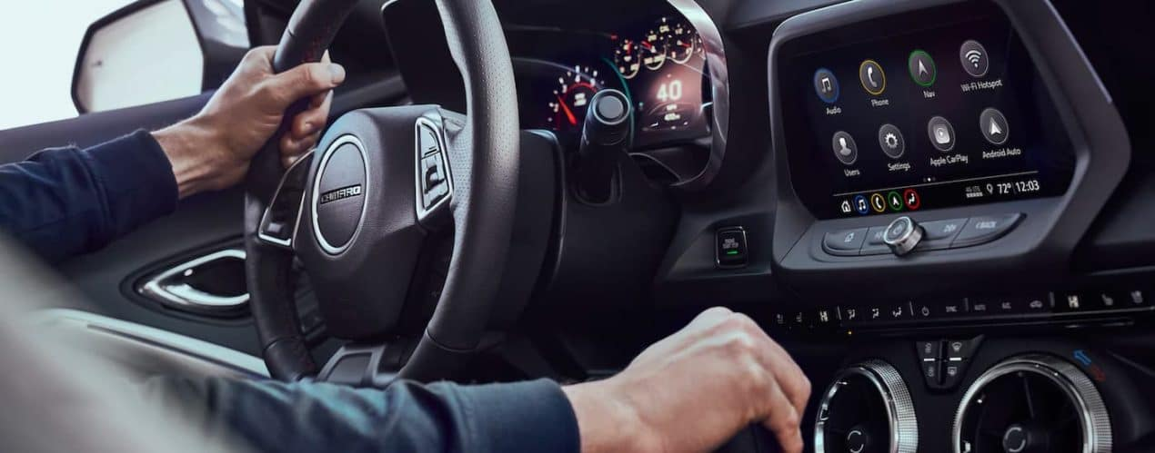 A close up shows a persons hand on the steering wheel and shifter in a 2021 Chevy Camaro 3LT Coupe.