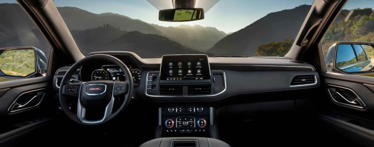 The front interior and dash is shown in a 2021 GMC Yukon SLT.